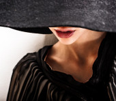 Beautiful woman with full lips in black hat poses on white background — Stock Photo