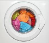 Wash machine with colored clothes inside — Stock Photo