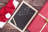 Santa claus hat, chalkboard and gift box on a wooden background — Stock Photo