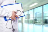 Doctor holding a clipboard and stethoscope at the hospital — Stock Photo