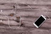 Smart phone with earphones — Stock Photo
