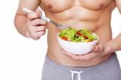 Strong fitness man holding a bowl of salad — Stock Photo