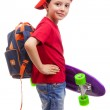 Smiling schoolkid standing with skateboard and backpack — Stock Photo #78165228