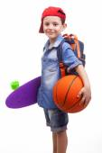 School kid holding a skateboard and a basketball — Stock Photo