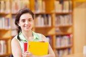女性学生が図書館でノートブックと立っています。 — ストック写真
