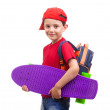 Smiling schoolkid standing with skateboard — Stock Photo #79976998