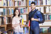 Portrait of smiling students at the library — Stock Photo