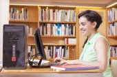 Student using the computer of the university library — Stock Photo