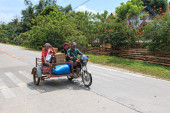 Puerto Princesa, Philippines - January 12,2015: Three people on a tricycle in the Philippines — Stock Photo