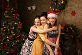 Portrait of  three young woman posing near decorated Christmas t — Stock Photo