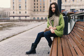 Beautiful modern woman with long brown hair sitting on bench — Stock Photo
