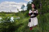 Sad pretty farmgirl looking far away near river. — Stock Photo
