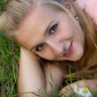 A happy laughing young woman laying on the grass — Stock Photo #78052782