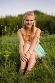 Beautiful girl sitting on a grass,  warm sunny day — Stock Photo