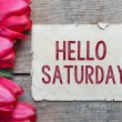 Постер, плакат: Tulips and paper with text Hello Saturday
