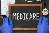 Doctor holding blackboard with the word medicare — Stock Photo