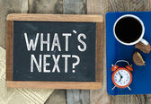 What's the next? sign on blackboard — Stockfoto