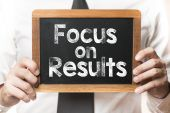 Businessman with focus on results  words — Stock Photo