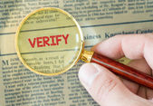 Verify word with magnifying glass — Stock Photo