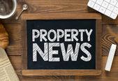 Property news handwritten on  blackboard — Foto de Stock