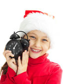 Portrait of a smiling little girl in a Santa hat is holding alar — Stockfoto