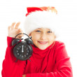 Little girl in Santa Claus hat holding alarm clock showing twelv — Stock Photo #57846887