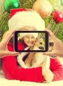 Little girl in Christmas clothes holding his dog and photographe — Stock Photo
