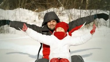 Father  and daughter sitting on the snow — Vídeo stock