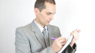 Бизнесмен, писать в блокноте — Стоковое видео