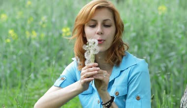 Girl blowing on a bouquet of dandelions — Stock Video