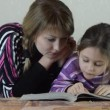 Mother and girl reading book — Stok video #61862181