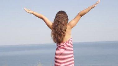 女の子に立って海ビーチ腕伸ばし — ストックビデオ