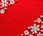 Snow flakes on red knitted fabric — Stock Photo
