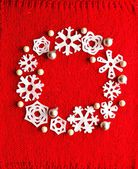 Snow flakes Christmas wreath on red knitted fabric — Stock Photo