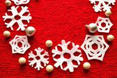Snow flakes Christmas wreath on red knitted fabric — Zdjęcie stockowe