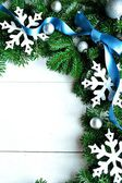 Snow flakes with blue ribbon on fir leaves.frame — Stock Photo