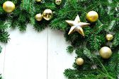 Gold Christmas ornament balls with star on fir leaves — Stockfoto