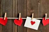 Red heart message card and red hearts with clothes pins — Stock Photo