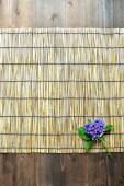 Blue hydrangea on bamboo blind — Stock Photo