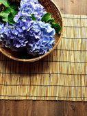 Bambu sepet bambu kör zemin üzerine mavi ortanca — Stok fotoğraf