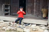 Small child sits on wooden hut step — Stock Photo