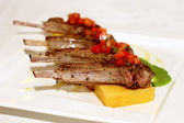 Grilled ribs with polenta on white plate — Stock Photo