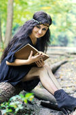Girl reading a book in the forest — Stock Photo
