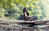 Smiling girl sitting on a log over the water  — Stock Photo