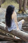 Girl sitting on a log in the forest — Stock Photo