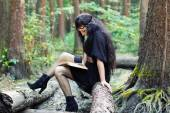 Girl reading a book in the green forest — 图库照片
