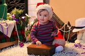 Baby in Santa hat sits on the carpet and openning a box — Stock Photo