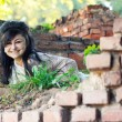 Laughing girl looks out of brick wall — Stock Photo #60085047