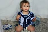 Indignant baby girl in the nautical striped vest sits on the car — Stock Photo