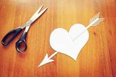 Paper heart pierced by an arrow on the table — Stockfoto